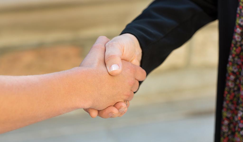 Kaksi asukasta kättelee.